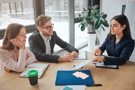 Young man and women sit together at table in meeting room. Brunette show paper to her colleagues. They look at it with attention.