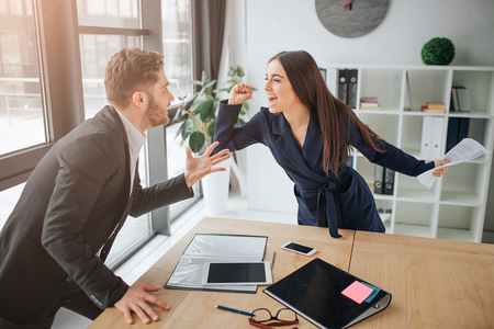 Argue between young man and woman. She scream and fight with guy. They stand in room at table. Materials lying on desk.