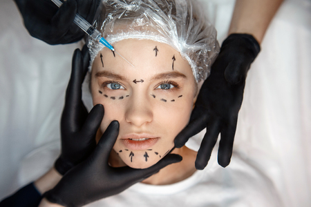Calm peaceful young woman lying on couch and look straight forward. Her face is marked. Three hands touching face skin. Fourth hold syringe for injection. Zdjęcie Seryjne