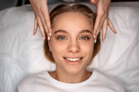 Cheerful attractive young woman lying on white couch. Beautician touch her face with bare hands. Model smile and look straight.