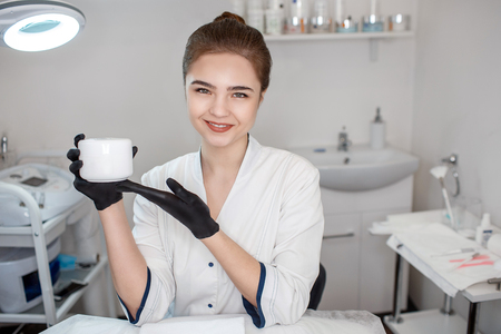 Nice young beautician hold jar of face cream. She look on camera smile and pose. Model sit in room. She point on cream jar.