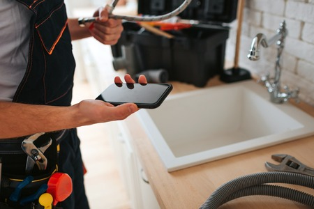 Cut view of man standing in kitchen at sink. He hold phone and wrench. Hose on desk. Stock Photo