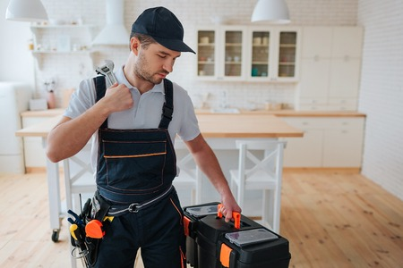 Serious young man stand in kitchen and look at tool box in his hand. Instruments on belt. Concentrated guy in uniform. Stockfoto
