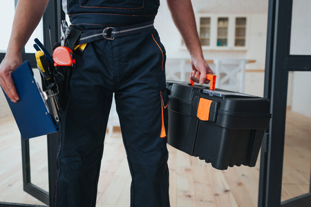 Cut view of handyman holding tool box and plastic tablet in hands. He stand in kitchen. Guy wear special uniform
