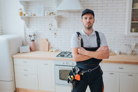 Plumber in kitchen. Professional look on camera and pose. Hands crossed. Tools on belt aside