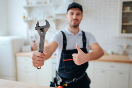 Young plumber hold wrench in hand. He show it to camera and hold big thumb up. Guy stand in kitchen. White background. Daylight
