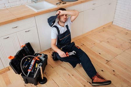 Tired exhausted plumber sit on floor in kitchen. He hold hand on forehead. Toolbox with wrech and other instruments stand on table