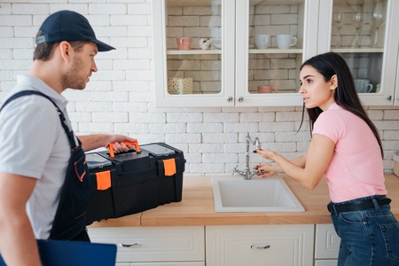 Young woman need help with sink in kitchen. She point on tap. Plumber stand beside her. He hold toolbox.