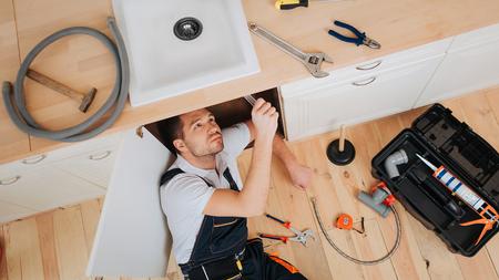 Jeune plombier regarde sous évier dans la cuisine. Il a mis un nouveau tuyau. Outils avec boîte ouverte au sol. Tuyau et clé avec pinces sur le bureau.