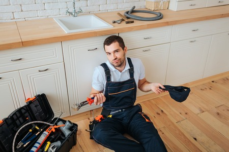 Handyman sit on floor in kitchen. He look on camera confusingly. Guy hold cap and wrench. Having rest.