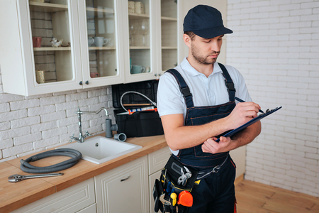 Busy young handyman stan in kitchen and white on plastic tablet. Toolbox and hose on desk. Daylight. Man in uniform. Imagens