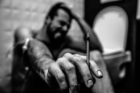 Black and white picture of young man in rest room sit and suffer. He show thin syringe in hand on camera. Guy scream and shrink. Pale weak body. Stock Photo
