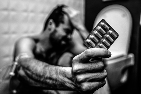 Black and white picture of young man sit on floor in rest room and hold plate of pills. Hand is wrapped with plait for taking drugs. Addiction and pain. Stock Photo