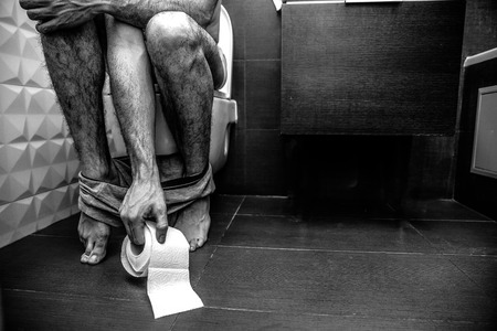 Cut view mans legs. Guy sit on toilet in rest room. He naked and have only shorts at his feet. Hand reach toilet paper. Black white picture, grey and colorless.