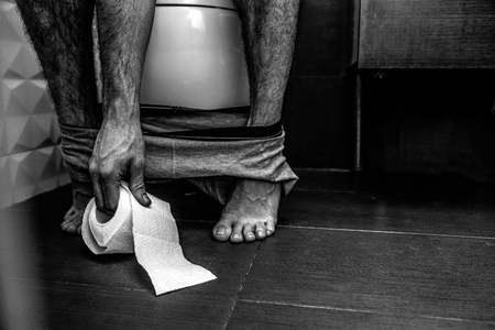 Cut view of balck and white picture. Man sit on toilet and reach paper. Legs are thin and pale. Problems with stomach. Constipation. Bed reaction. Suffer. Colorless.