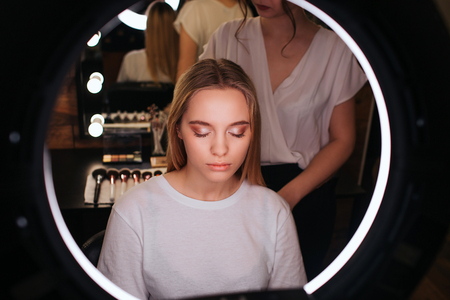 Look in mirror. Young blonde woman keep eyes closed. She has eyeshadows on eyeline. Hairdresser stand behind her and pull hair up. Stok Fotoğraf