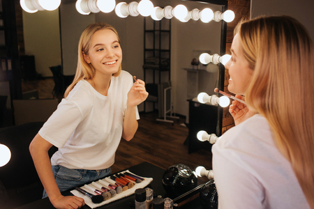 Nice cheerful young woman look in mirror in beauty room and smile. She hold brush for eyeshadows.