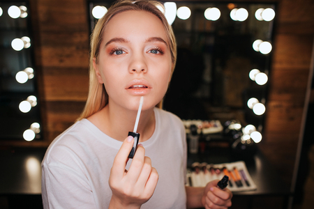Young blonde woman applying lipgloss on lips. She look on camera. Serious and concentrated. Mirror with light bulbs behind.