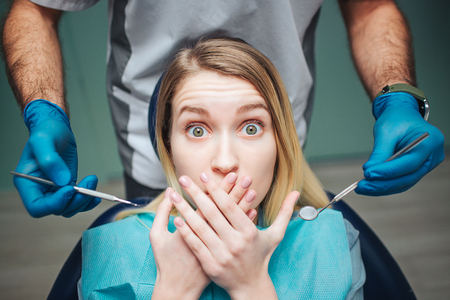 Young woman sit inchair in dentistry. She afraid and cover mouth with hands. Client look on camera with fear in eyes. Male dentist hold equipment for teeth treatment.