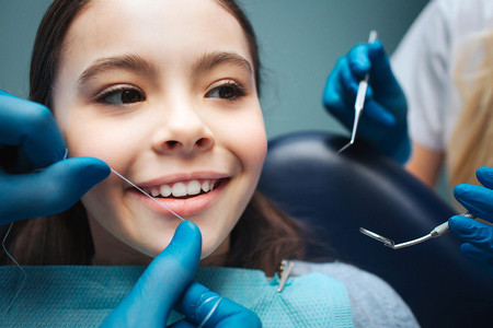 Close up girl in dental chair. Hand to floss front teeth. Womans hands hold tools. 스톡 콘텐츠