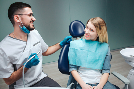 Happy young female client sit in chair in dentistry. She look at dentist and smile. Young man in mask and white rob holding machine for teeth treatment.