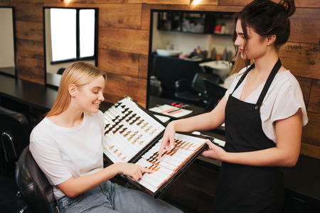 Smiling blonde young woman and hairdresser choosing hair color from palette before professional coloring in beauty salon. Beauty, hair dyeing and people concept