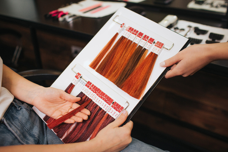 Hair color chart at beauty salon. Female client with hairdresser choosing red color hair from palette samples before coloring close-up
