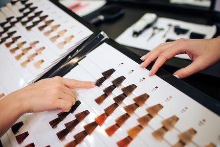 Gros plan sur une femme choisissant des cheveux de couleur foncée dans une palette sur fond blanc avant de colorer