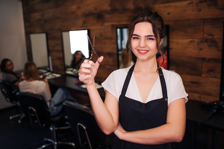 Portret of happy beautiful woman hairdresser with black apron with black apron looking at camera while holding professional scissor on beauty salon background. Selective focus