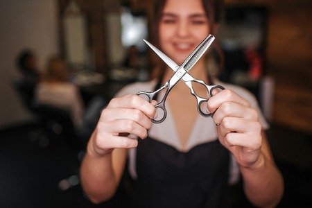 Close-up of professional metal hairdressing cutting scissors in hairdresser hands. Hairdressing tool on foreground Stock Photo - 119326245