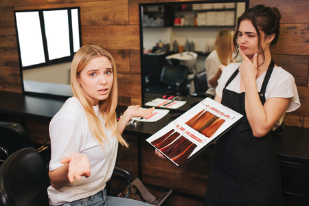 Confused blonde young woman cant choosing color hair from palette before professional coloring in beauty salon. Beauty, hair dyeing and people concept