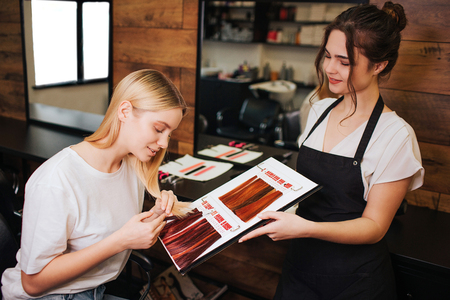 Young beautiful woman and hairdresser comparing her blonde hair with color hair from palette before correct coloring. Beauty, hair dyeing concept