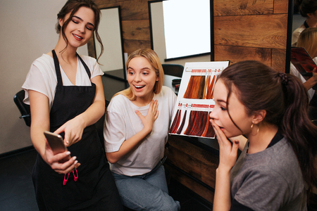 Surprised young women looking at phone while hairdresser holding it in hand. Hairstylist proposing fashion hair coloring in salon Zdjęcie Seryjne