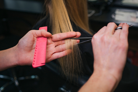 Close-up of hairdressers hand cutting blonde hair. Doing professional haircut in beauty salon