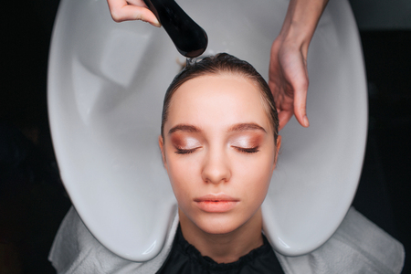 Top view of beautiful young woman with closed eyes sitting on white hair wash sink while hairdresser washing blonde hair close-up. Hair care in salon