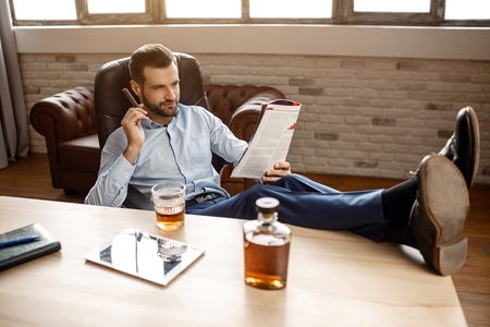 Young handsome businessman sit on chair and read journal in his own office. He hold cigar in hand and legs on table. Tablet with glass of whiskey and graphene stand together.