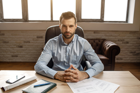 Young handsome businessman sit at table and pose in his own office. He look straight on camera. Notebook journal and phone on desk Stock Photo
