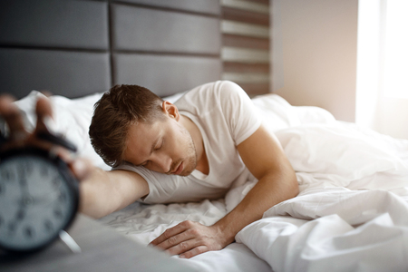 Young man sleep on bed in morning. He hold hand on clock. Oversleep. Daylight.
