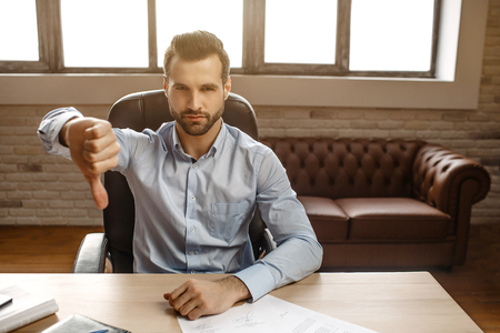Young serious handsome businessman sit at table in his own office. He hold big thumb down and look serious on camera. Bright window behind.