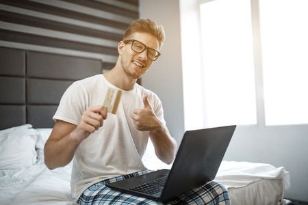 Cheerful positive young man sit at edge of bed this morning. He look on camera and smile. Guy hold credit card and show big thumb up. Laptop on knees