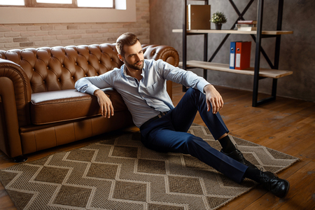 Young handsome businessman sit on floor and pose in his own office. He look straight with confidence. Sexy young man lean to sofa Stock Photo