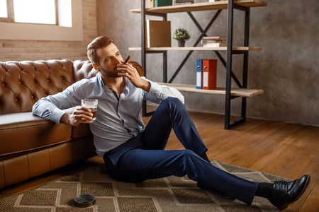 Young handsome businessman smoke cigar and hold glass of whiskey in his own office. He sit on floor and look confident. Sexy young man relaxing Stock Photo