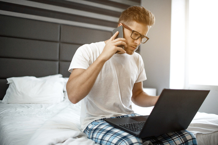 Busy young man sit on bed early morning. Guy talk on phone. He look on laptop and type on keyboard. Serious and concentrated. Business. Daylight