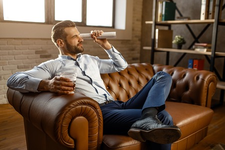 Young handsome businessman sit on sofa and play in his own office. He look straight through rolled journal. Guy hold glass with whiskey in hand. Leg on another one. Confidence Stock Photo