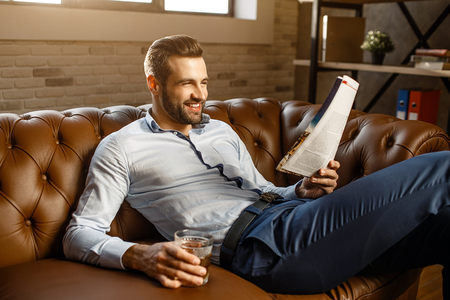 Young handsome businessman sit on sofa and read in his own office. He hold glass of whiskey in hand and smile. Positive and happy. Good-looking