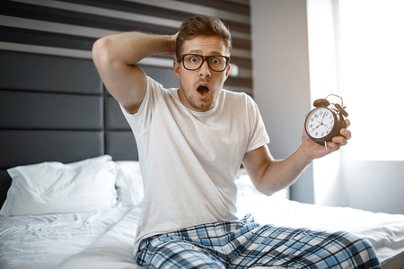 Amazed and scarec young man on bed in morning. He look emotionally on camera. Guy hold clock in hand Stock Photo