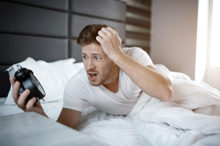 Emotional young man on bed in early morning. He overslept. Guy hold clock and look at it scared