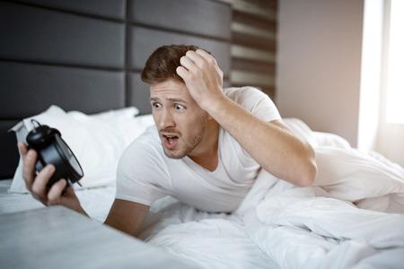Emotionaler junger Mann am frühen Morgen auf dem Bett. Er hat verschlafen. Kerl hält die Uhr und schaut sie erschrocken an