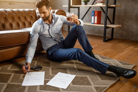 Young handsome businessman put signature on papers in his own office. He sit on floor and hold glass of whiskey in hand. Nice and confident sexy young man