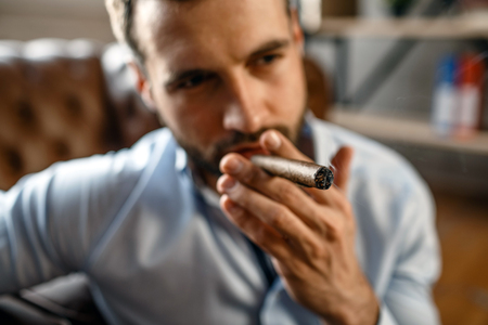Portrait and close up of young handsome businessman in his own office. He smoke cigar. Guy sit on floor with confidence. Concentrated and cool